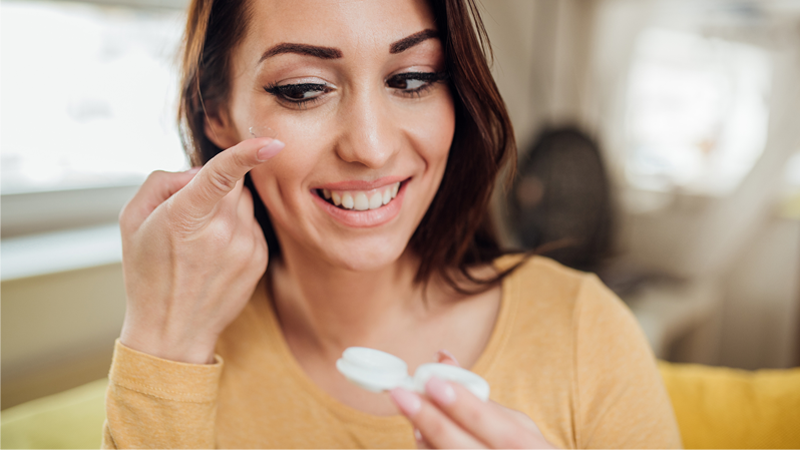 woman holding a contact lens