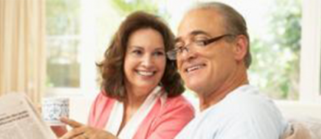 mature man and woman smiling and reading a newspaper