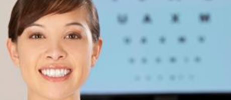 eye care practitioner smiling in front of an eye exam chart
