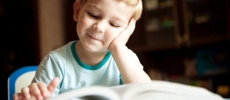 young boy smiling and reading