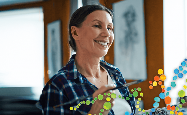 mature woman smiling and painting