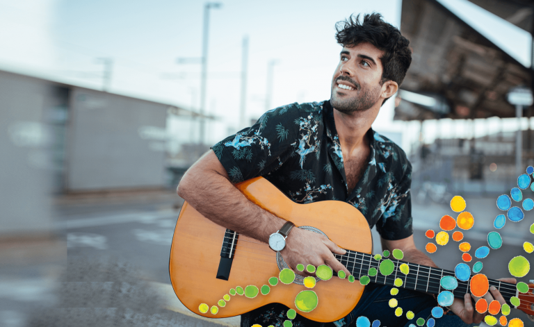 man smiling and playing the guitar