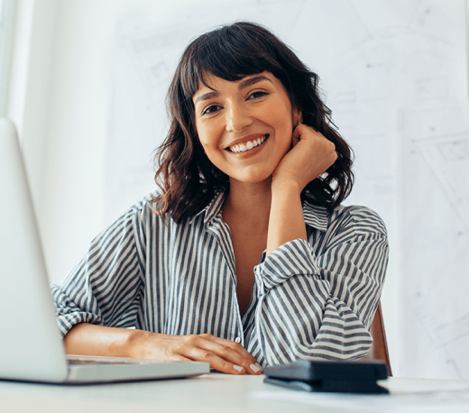 woman smiling and using a laptop